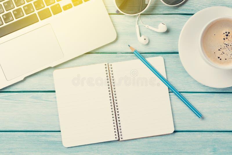 Scrittorio con il computer portatile, il caffè ed il blocco note fotografie stock