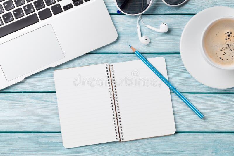 Scrittorio con il computer portatile, il caffè ed il blocco note fotografia stock
