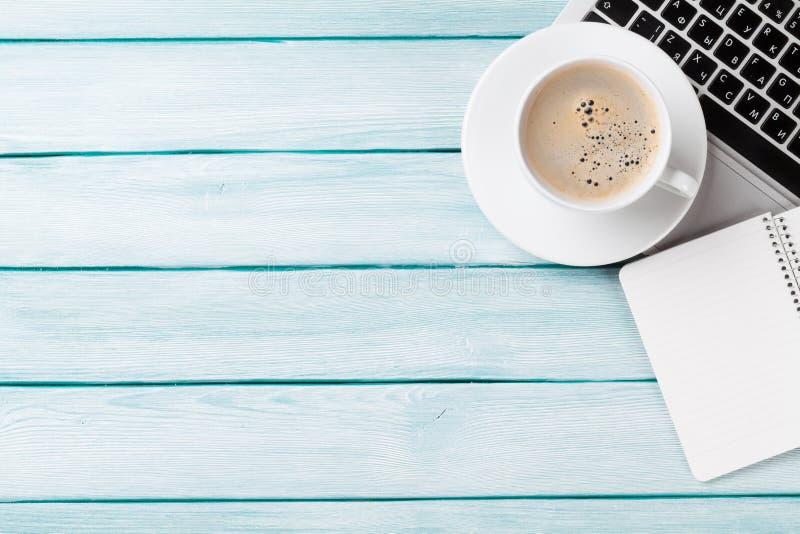 Scrittorio con il computer portatile, il caffè ed il blocco note immagini stock