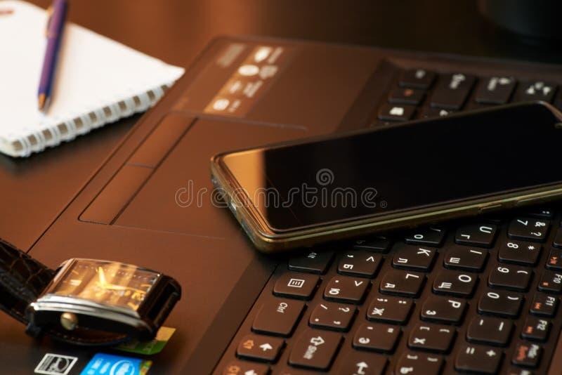 Scrittorio con il computer portatile, lo Smart Phone, i taccuini, le penne, gli occhiali e una tazza di tè Vista di angolo latera immagini stock libere da diritti