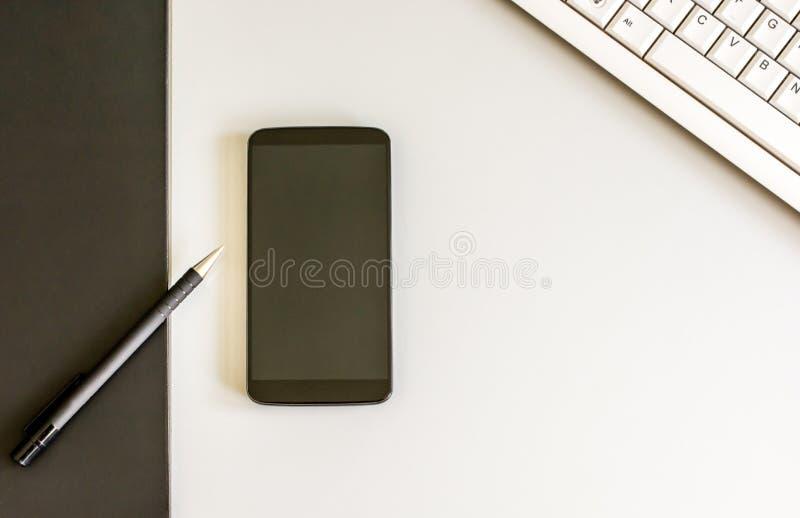 Scrittorio con la tastiera dello smartphone, della penna e di computer veduta da sopra fotografia stock
