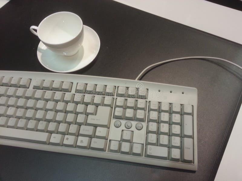 scrittorio con la tastiera e la tazza immagine stock libera da diritti