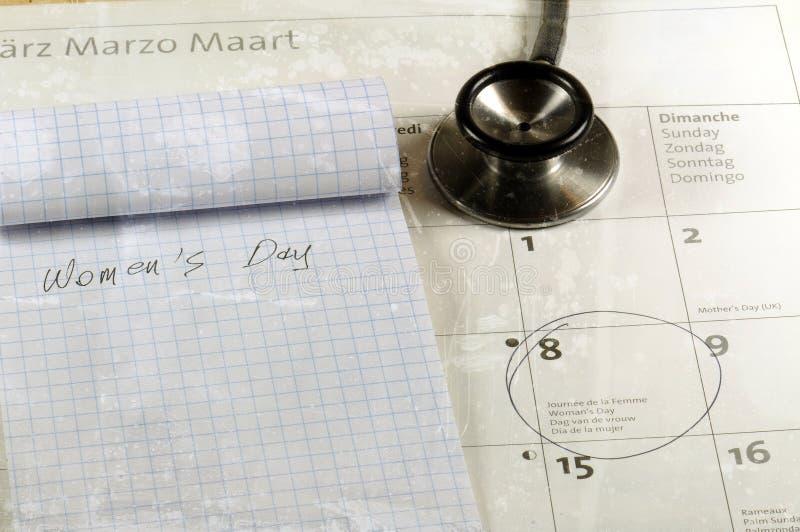 Scrittorio con lo stetoscopio, il calendario ed il taccuino Concetto di giorno del ` s delle donne fotografia stock