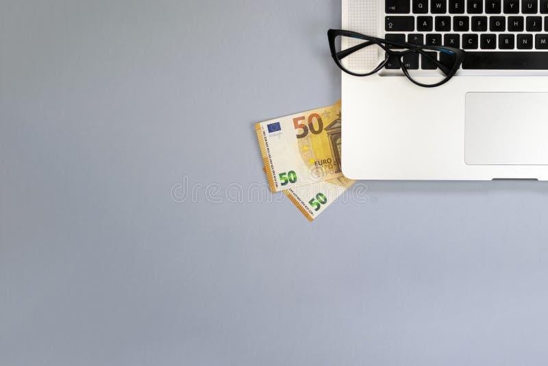 Scrittorio con soldi, computer portatile, vetri fotografie stock