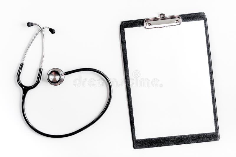 Scrittorio del lavoro del ` s di medico in ospedale con il modello bianco di vista superiore del fondo dello stetoscopio e del bl immagini stock libere da diritti