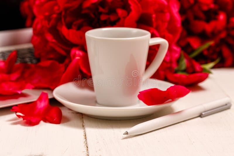 Scrittorio del Ministero degli Interni con il computer portatile, peonie rosa, tazza di caffè, cancelleria, vetri su un fondo bia fotografia stock