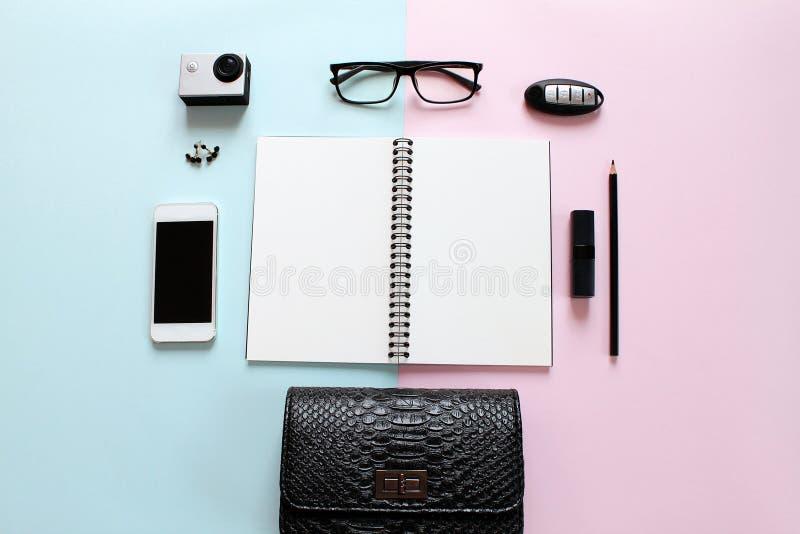 Scrittorio dell'area di lavoro con il taccuino in bianco, la matita, il rossetto, la chiave dell'automobile, i vetri dell'occhio, fotografia stock