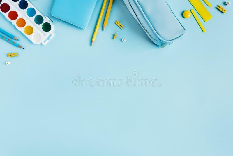 Scrittorio della scuola con i materiali di scrittura sparsi fotografia stock libera da diritti