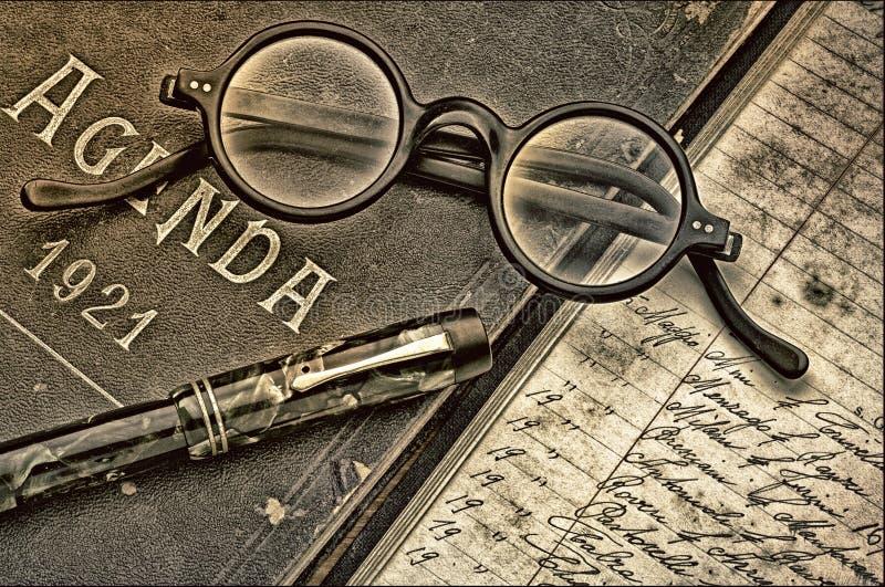 Scrittorio dello scrittore, annata di ordine del giorno, occhiali e penna stilografica royalty illustrazione gratis