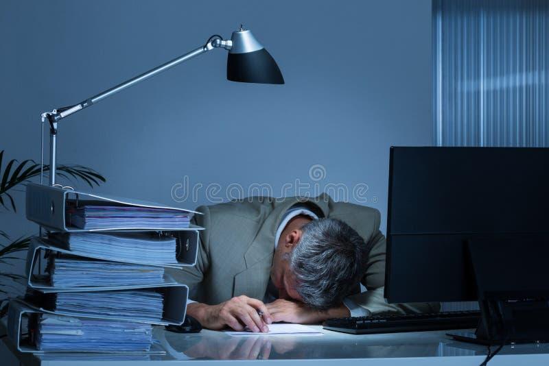 Scrittorio di Leaning Head On dell'uomo d'affari dai raccoglitori mentre lavorando tardi fotografia stock libera da diritti