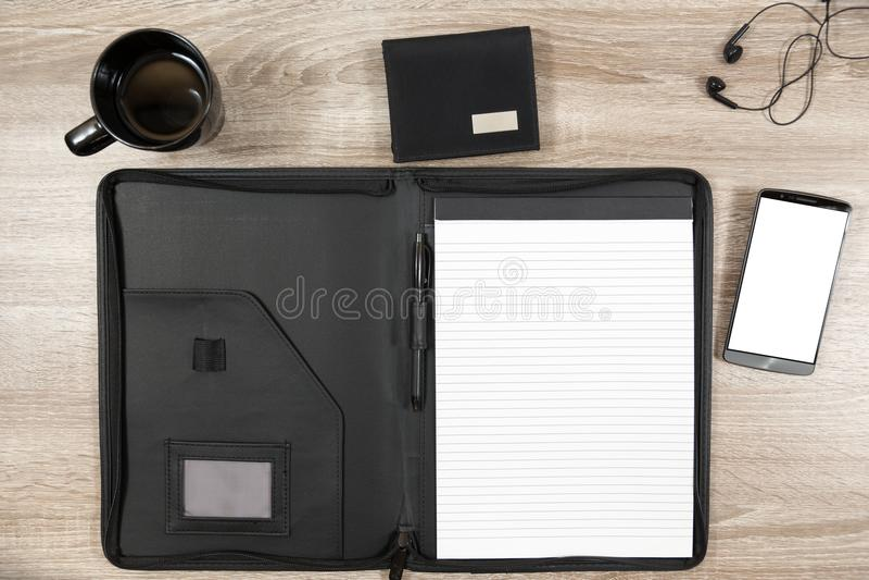 Scrittorio di legno con lo smartphone, cuffie, portafoglio, tazza da caffè e immagine stock