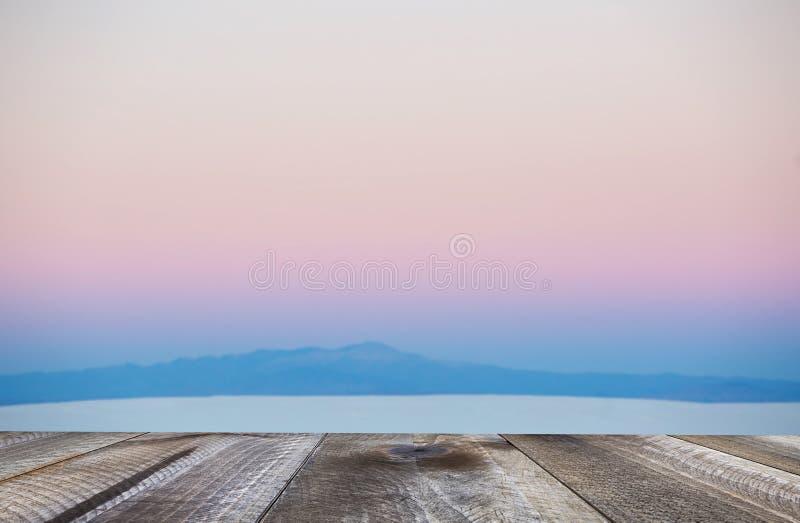 Scrittorio di legno con spazio libero e fondo vago di paesaggio al tramonto immagine stock libera da diritti