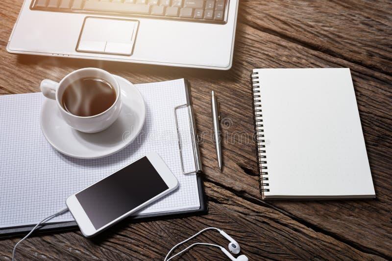 Scrittorio di legno dell'ufficio con la penna, blocco note, tazza di caffè, smartphone e fotografia stock