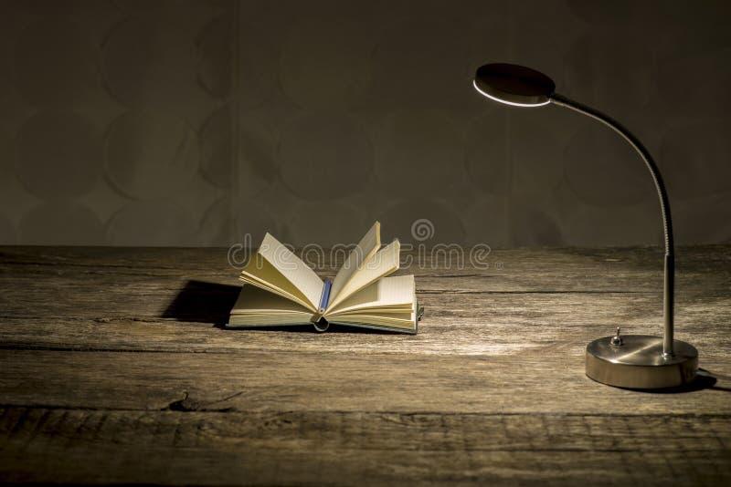 Scrittorio di legno rustico di studio con la lampada da tavolo accesa ed il taccuino aperto immagini stock libere da diritti