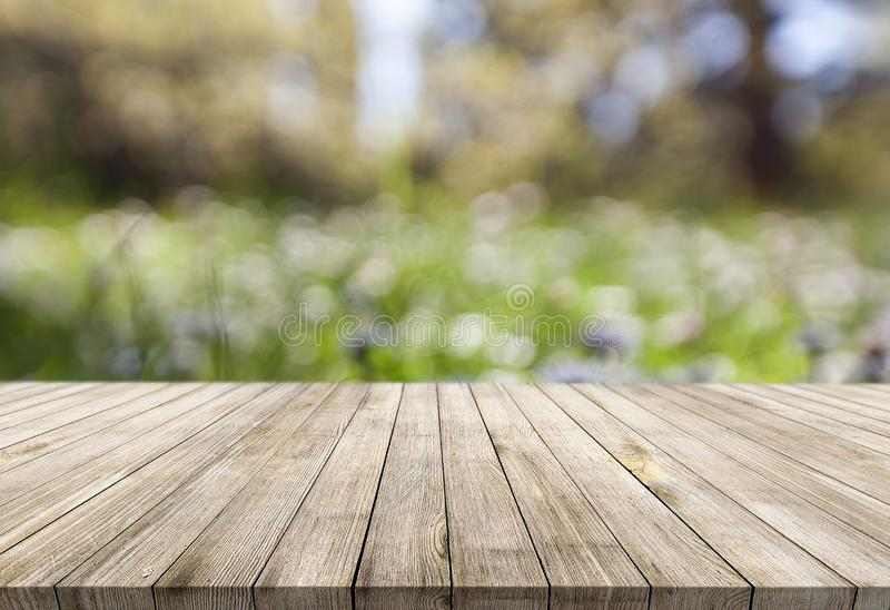 Scrittorio di legno sullo sfondo naturale astratto della sfuocatura del bokeh fotografia stock libera da diritti