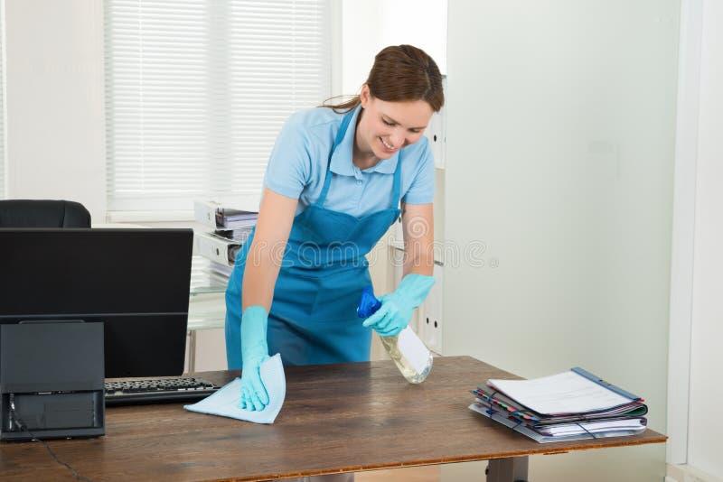 Scrittorio di pulizia del lavoratore con lo straccio