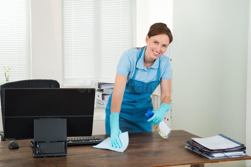 Scrittorio di pulizia del lavoratore con lo straccio fotografia stock libera da diritti