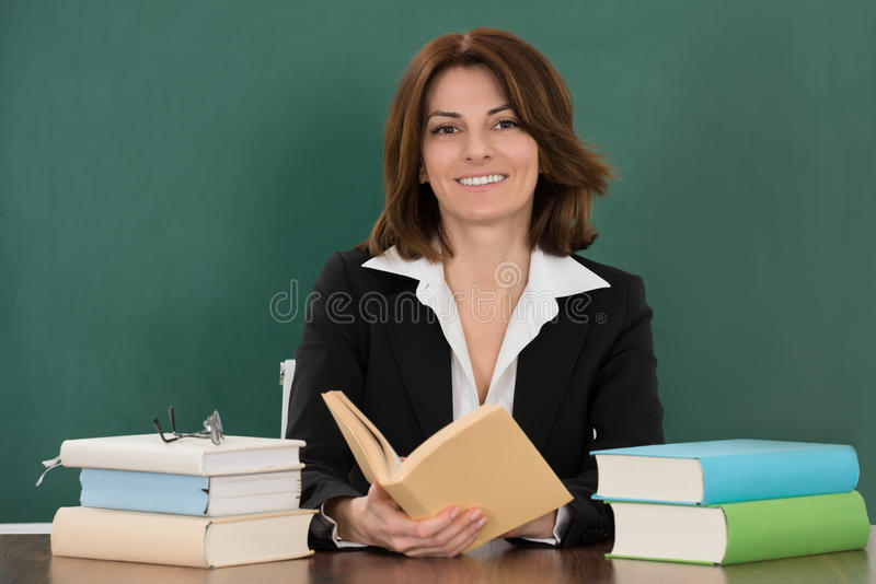 Scrittorio di Sitting At Classroom dell'insegnante femminile immagini stock libere da diritti