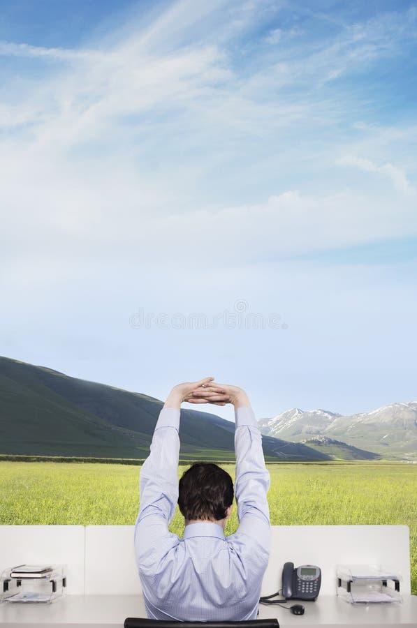 Scrittorio di Stretching At Office dell'uomo d'affari sul campo immagini stock libere da diritti