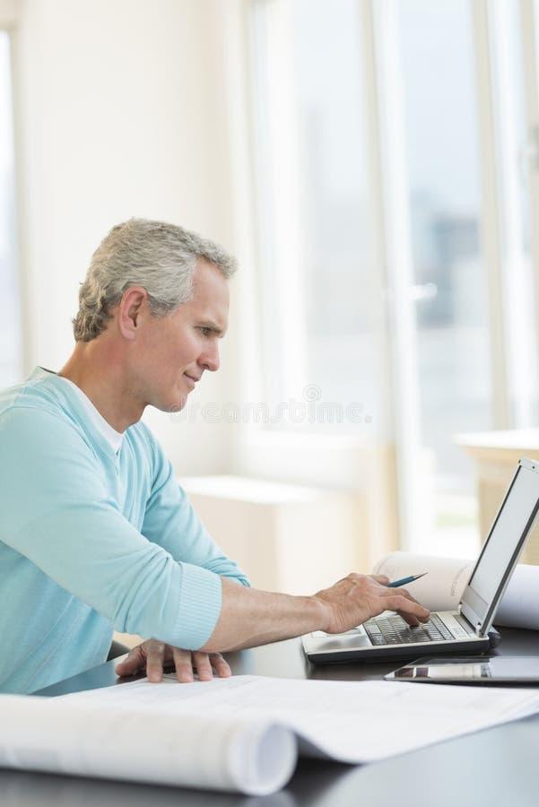 Scrittorio di Using Laptop At dell'architetto fotografia stock
