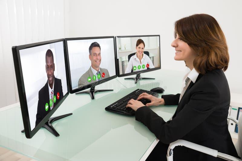 Scrittorio di Video Conferencing On della donna di affari immagini stock