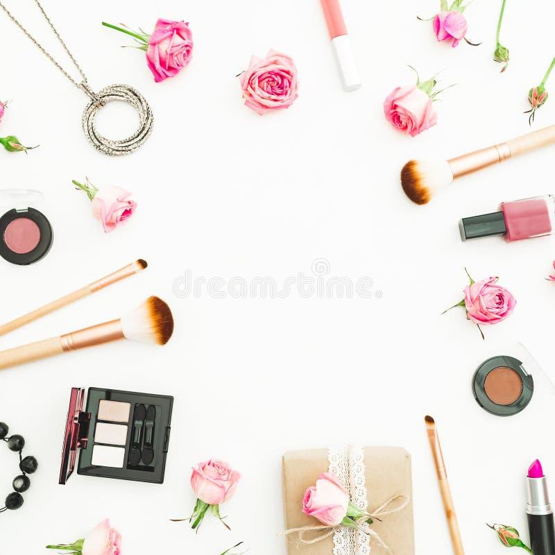 Scrittorio femminile con il contenitore di regalo, rose rosa, cosmetici, diario su fondo bianco Vista superiore Disposizione pian immagini stock libere da diritti