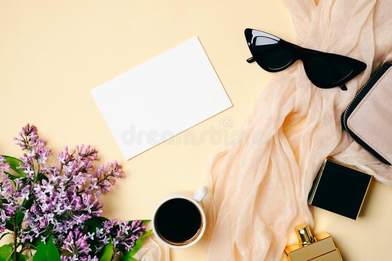 Scrittorio femminile con la carta di Libro Bianco, la sciarpa di seta, la bottiglia di profumo, la tazza di caffè, gli occhiali d immagini stock libere da diritti