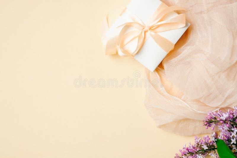 Scrittorio femminile con la sciarpa di seta, il contenitore di regalo ed i fiori lilla su fondo beige Vista superiore, composizio immagini stock libere da diritti