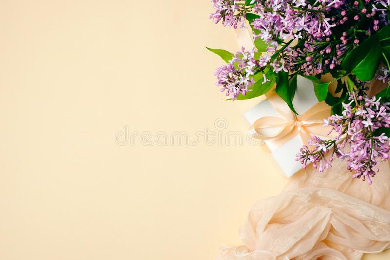 Scrittorio femminile con la sciarpa di seta, il contenitore di regalo ed i fiori lilla su fondo beige Vista superiore, composizio fotografia stock libera da diritti