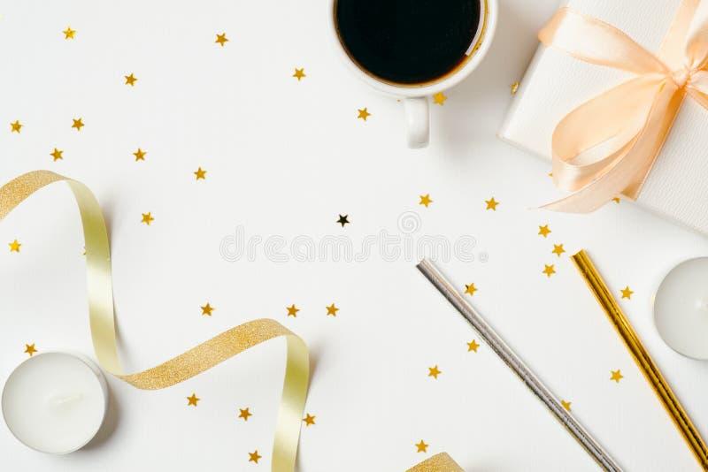 Scrittorio femminile di vista superiore con gli accessori della tazza e del partito di caffè: nastro, paglia della bevanda, conte immagini stock