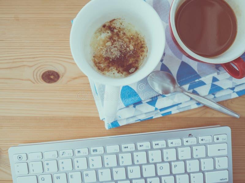 Scrittorio funzionante con il caffè della prima colazione fotografia stock