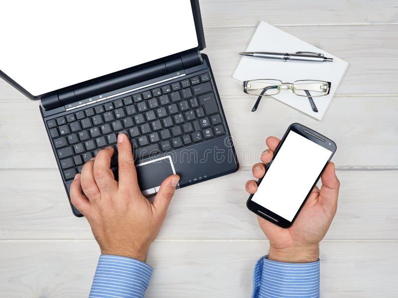 Scrittorio funzionante dell'uomo d'affari di vista superiore con lo smartphone del computer portatile immagine stock