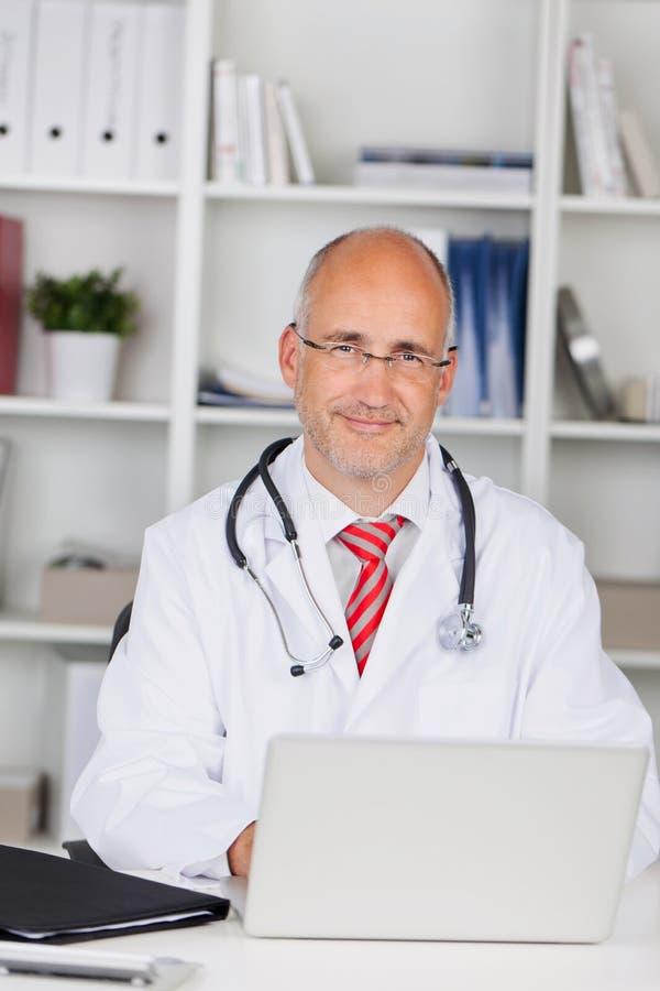 Scrittorio maschio sicuro del dottore With Laptop At fotografia stock