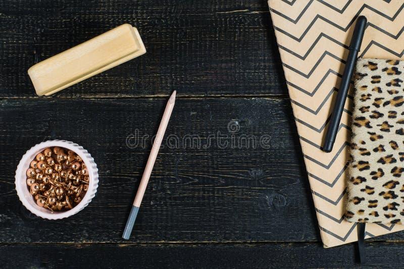 Scrittorio piano del Ministero degli Interni di disposizione Area di lavoro femminile con gli accessori dorati, diario su fondo n fotografie stock