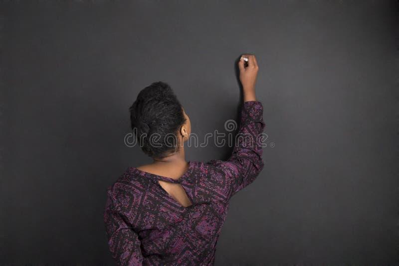 Scrittura afroamericana dell'insegnante della donna sul fondo del bordo del nero del gesso fotografia stock
