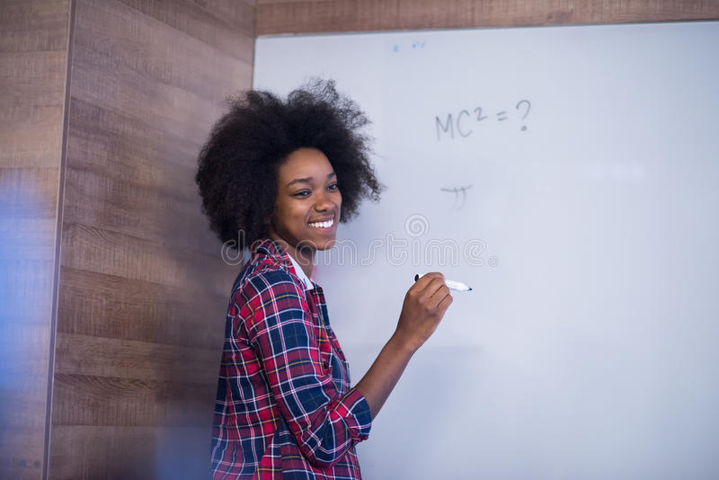 Scrittura afroamericana della donna su una lavagna in un offic moderno immagine stock libera da diritti
