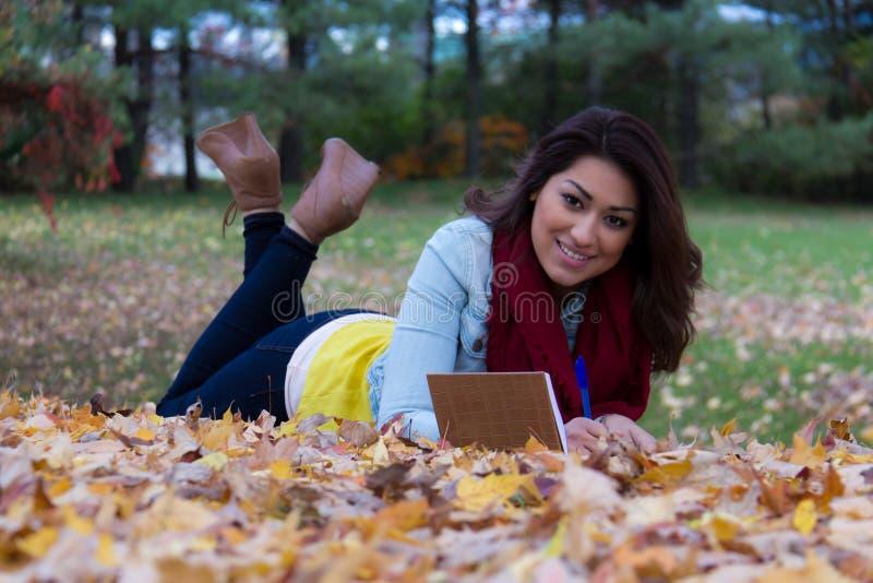Scrittura alla moda della donna in suo taccuino all'aperto durante l'autunno fotografia stock