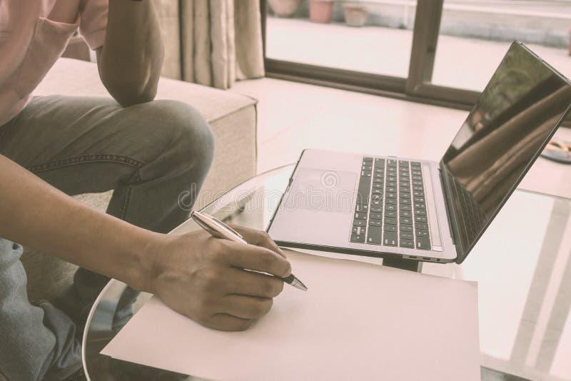 Scrittura anonima del lavoratore su un foglio di carta di progetto di lavoro di affari sulla scrivania Il computer portatile è di fotografia stock libera da diritti