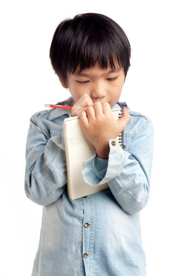 Scrittura asiatica del ragazzo sul taccuino immagine stock libera da diritti
