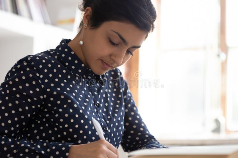 Scrittura astuta della studentessa che studia a casa immagini stock