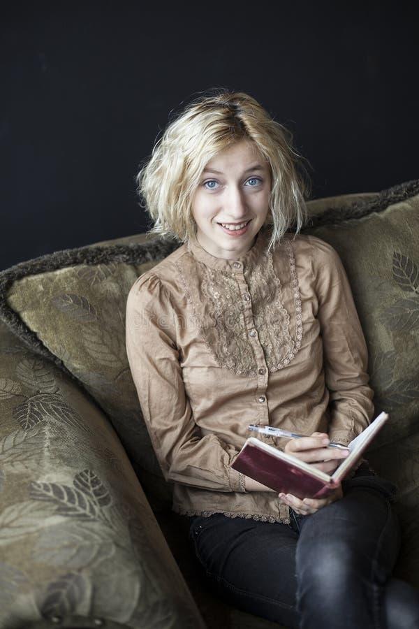 Scrittura bionda della giovane donna in suo giornale fotografia stock