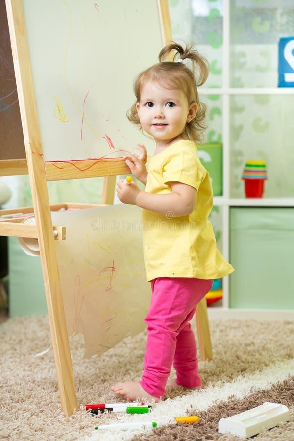 Scrittura del bambino sulla lavagna in scuola materna fotografie stock