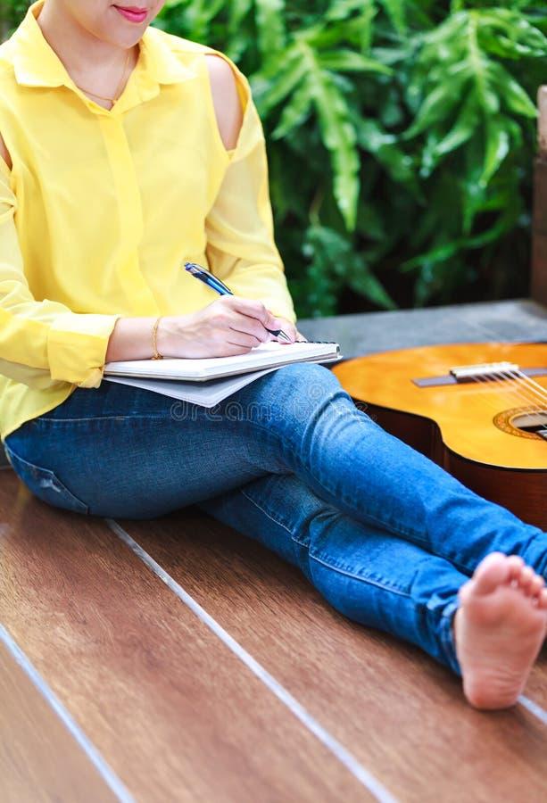 Scrittura del cantautore del primo piano sulla carta per appunti con il Ne della chitarra acustica fotografie stock libere da diritti