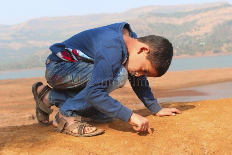 Scrittura del ragazzino sulla terra con il suo dito al ghat di Tamihini, Pune fotografie stock