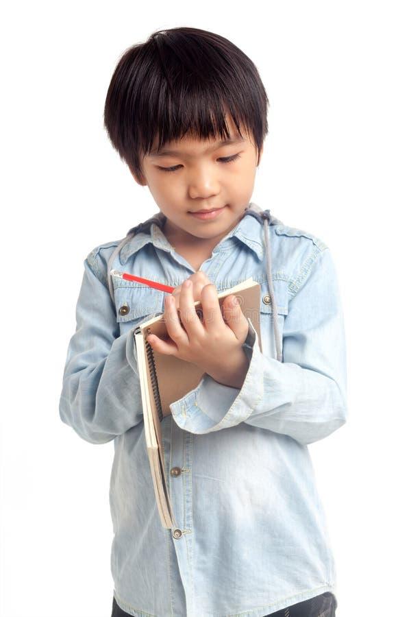 Scrittura del ragazzo sul taccuino immagine stock libera da diritti
