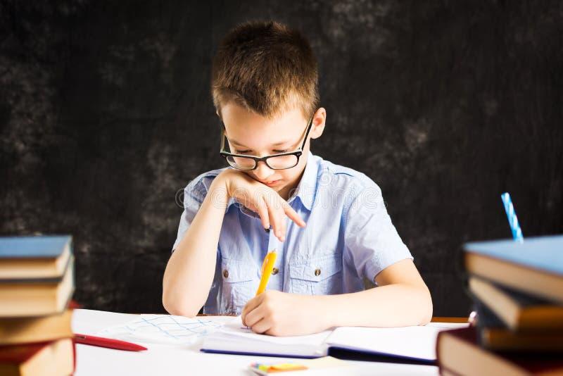 Scrittura del ragazzo in taccuino sullo scrittorio coperto in libri immagine stock