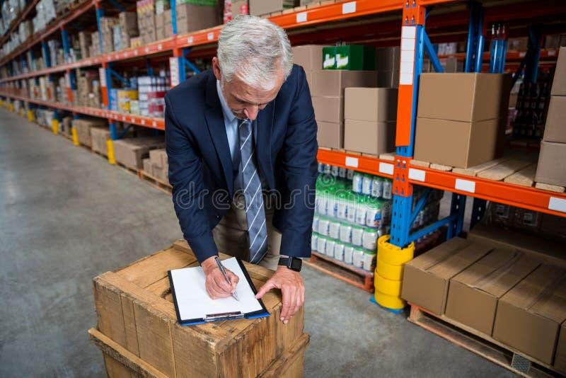 Scrittura del responsabile sulla sua lavagna per appunti illustrazione di stock
