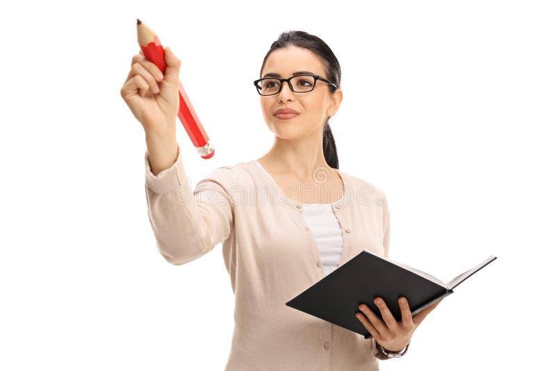 Scrittura dell'insegnante femminile con una grande matita rossa fotografie stock libere da diritti