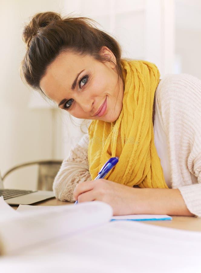 Scrittura dell'interno sorridente della donna sul suo blocchetto per appunti immagini stock libere da diritti