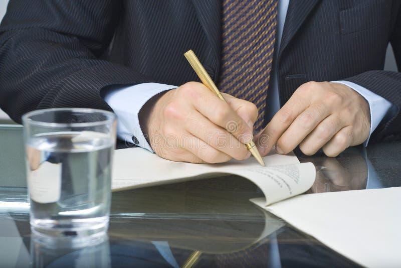 Scrittura dell'uomo d'affari in un documento immagine stock